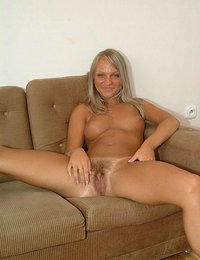 Sexy blonde naked on the couch to show off her sultry tits and hairy pussy slit