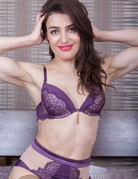 Julia Red is lovely in her purple lingerie, relaxing in bed. She strips off her lingerie and stockings, and we enjoy her body. Her natural breasts and very hairy pussy shine as she lays naked in bed.